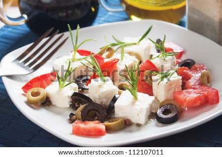 Mediterranean feta cheese salad with tomato, olives and rosemary