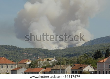 Mediterranean forest fire with smoke cloud over the city - stock photo