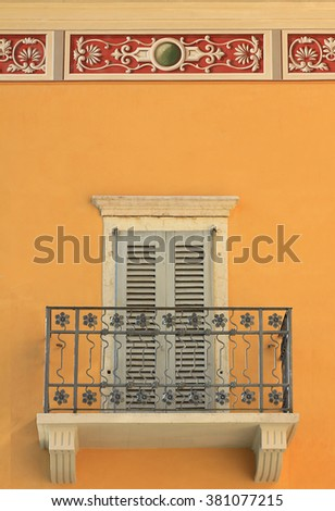 mediterranean house facade with balcony, closed shutters and ornamental stucco border - stock photo