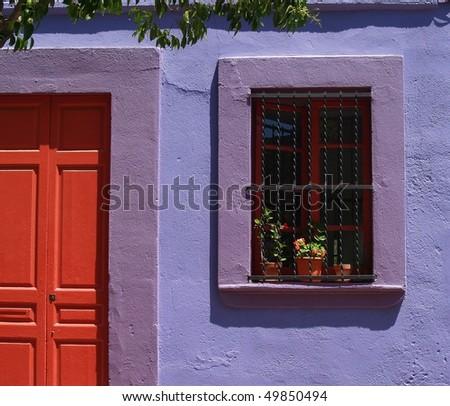 Mediterranean house facade with red door and window - stock photo