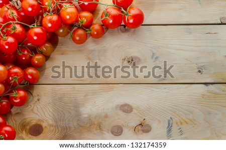 Mediterranean ingredients: ripe tomatoes on rustic wood table. Plenty of copyspace, perfect for a menu. Landscape orientation. - stock photo