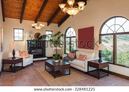 Mediterranean living room in beige with sofa, wooden stands, fireplace place, coffee table and wooden ceiling. - stock photo