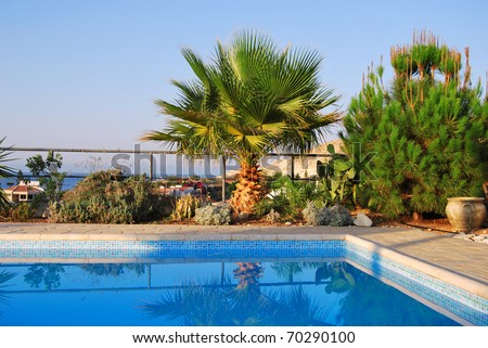 Mediterranean Luxury swimming pool surrounded by lush tropical plants, palm and pine over blue sky sea and sky background in the morning, Cyprus - stock photo