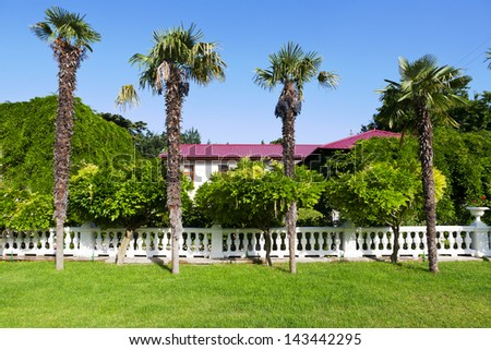 Mediterranean mansion is surrounded by greenery under the blue sky - stock photo