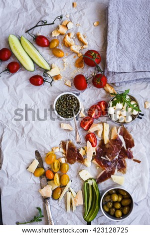 Mediterranean mix antipasto or snacks for dinner party. Vegetables, variety cheese, ham, olive fruit, mozzarella cheese, arugula leaves, tomatoes cherry. Top view.   - stock photo