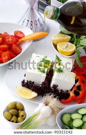 Mediterranean salad with tomatoes, olives, cheese and a lemon, served on a white table, with olive oil pouring on a peaces of cheese