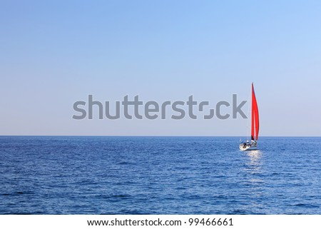 Mediterranean Sea Scene. Magnificent lonely yacht with red sail - stock photo