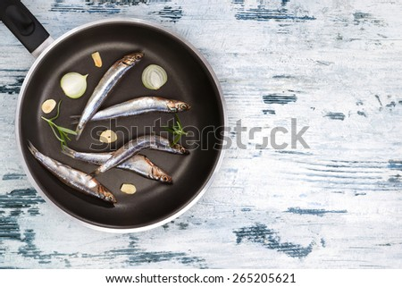 Mediterranean seafood eating. Fresh sardines on black pan on white and blue textured wooden background top view. Seafood background.  - stock photo