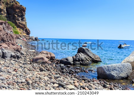 Mediterranean shoreline of colorful pebbles. There are some boats slightly off - stock photo