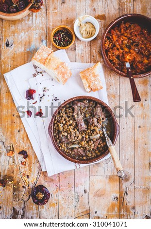 Mediterranean simple homemade food concept. Beef meat cooked with Lentils, vegetables, smoked sausage served in ceramic bowl over on rustic table from above with bowl of vegetable meat. Rustic style.  - stock photo