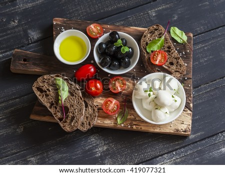 Mediterranean snack - mozzarella, olives, rye ciabatta bread, cherry tomatoes on a rustic wooden cutting board on a dark background - stock photo