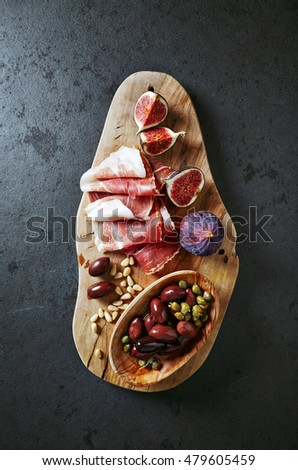 Mediterranean-style antipasto on a wooden chopping board (from above)