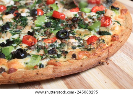 Mediterranean style pizza with chicken and various vegetables on a wooden cutting board  - stock photo
