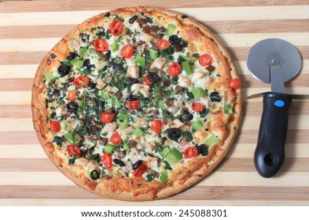 Mediterranean style pizza with chicken and various vegetables on a wooden cutting board with cutter on the side - stock photo