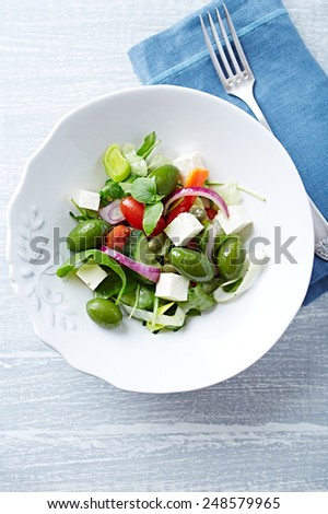 Mediterranean-style salad with feta and green olives - stock photo