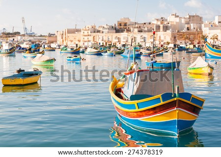 Mediterranean traditional colorful boats luzzu. Fisherman village in the south east of Malta. Early winter morning in Marsaxlokk, Malta. - stock photo