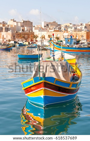 Mediterranean traditional colorful boats luzzu. Fisherman village in the south east of Malta. Early winter morning in Marsaxlokk, Malta.