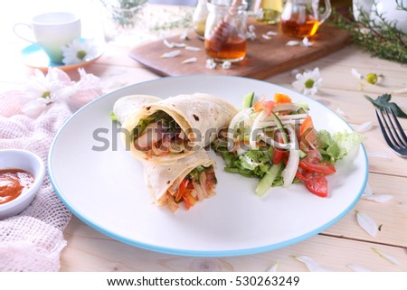 Mediterranean wrap filled with lettuce, zucchini, eggplant, onions, mushrooms, tomatoes and feta cheese, served with hot sauce and salad.