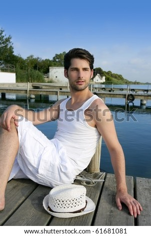 Mediterranean young latin man relaxed on wood pier white hat - stock photo
