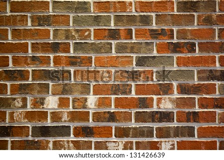 Medium close up image of an antiqued red and multi-colored brick wall. The image shows the texture of the brick and mortar between the rows of bricks. - stock photo