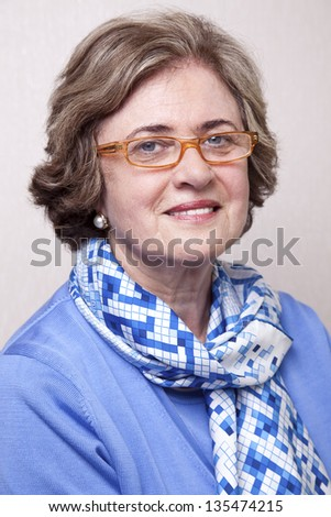Medium close-up portrait of an elegant amd well maintained senior woman (in her late 60's) wearing glasses, smiling a toothy smile to the camera. - stock photo