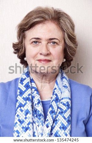 Medium close-up portrait of an elegant and well maintained senior woman (in her late 60's) slightly smiling to the camera. - stock photo
