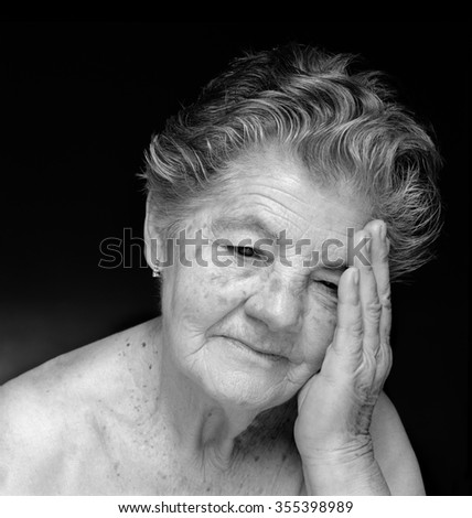 Medium format film photography shot. Black and white portrait of melancholic and meditative elderly woman against black background.