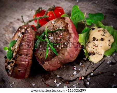 Medium grilled bbq steaks with fresh herbs and tomatoes - stock photo