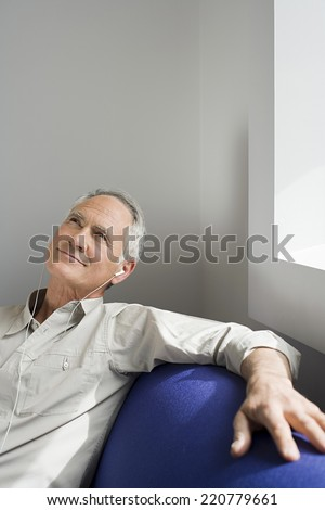 Medium portrait of man enjoying listening to music on headphones seated on sofa - stock photo