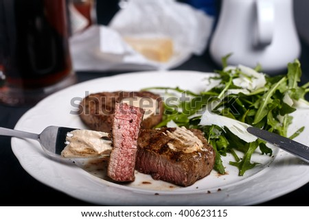 Medium-rare beef filet grilled with fresh arugula salad leaves on white plate. Sauce and parmesan on background. - stock photo