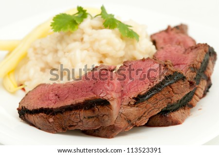 medium rare beef tenderloin grilled to perfection with creamy risotto and yellow string beans - stock photo