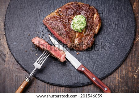 Medium rare grilled Beef steak with herb butter on fork on dark background - stock photo
