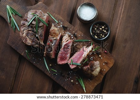 Medium rare grilled ribeye beef steak over rustic wooden surface, high angle view - stock photo