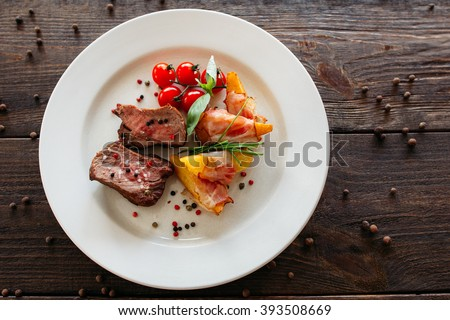 Medium rare pork steak with fresh vegetables. Food fotography of pork steak with potatoes and tomatoes cherry. Tasty cook meat with vegetables on dark wooden background.  - stock photo