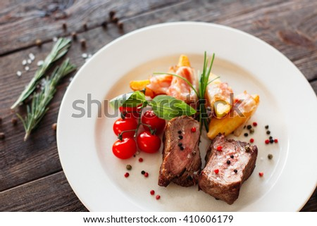 Medium rare pork steak with fresh vegetables on white plate. Top view food photography of pork steak with potatoes and tomatoes cherry. Prepared meat with vegetables on dark wooden background.  - stock photo