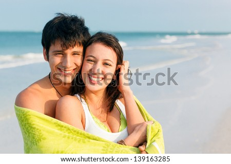 Medium shot of happy, smiling young latin couple on Beach wrapped in Green Towel. Ft. DeSoto Beach, Florida, USA. - stock photo