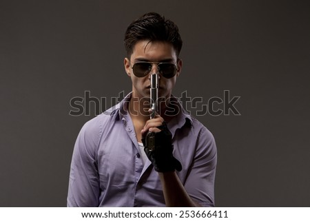 medium shot of shooter or contractor wearing glasses and holding gun near face - stock photo