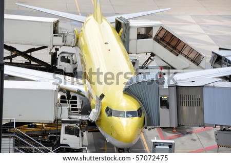 Medium size airplane being serviced at the gate - catering being delivered, service checks being performed - stock photo