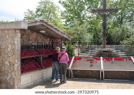 MEDJUGORJE, BOSNIA AND HERZEGOVINA, MAY 12, 2010 - Pilgrims at reverent place next to the Saint James church of Medjugorje - stock photo