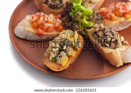 Medley bruschetta topping with sauteed mushroom/ garlic butter clam/ tomato salsa on wood plate, on white. - stock photo