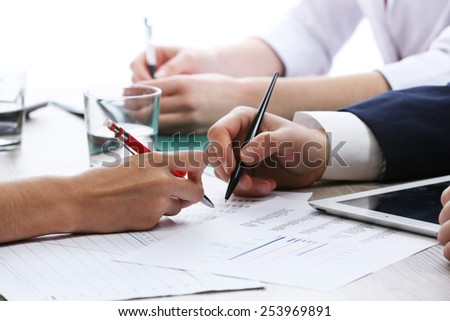 Meeting at worktable on white blurred background - stock photo
