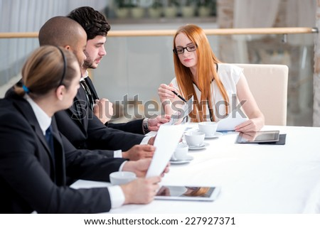 Meeting business partners in the office. Four smiling successful businessmen sitting at table in office while discussing their of business doings. Young people talking in office