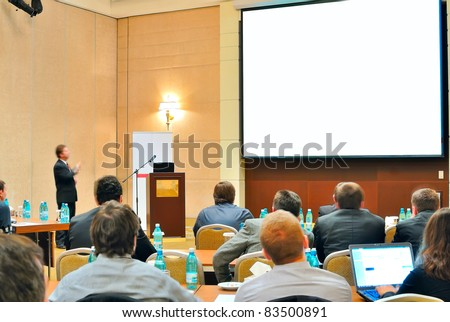 meeting, conference, presentation in auditorium with blank screen