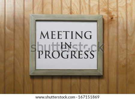 meeting in progress sign on wall - stock photo
