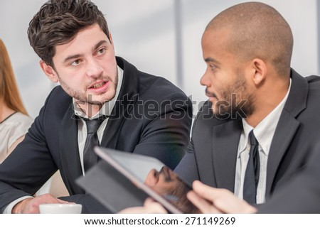 Meeting of four confident young people. Four confident successful businessmen at a meeting while sitting at a table discussing business case in the office showing thumbs up - stock photo