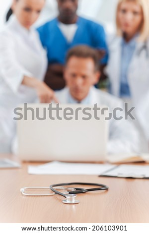 Meeting of medical experts. Group of confident doctors discussing something and looking at the laptop while stethoscope laying on foreground - stock photo