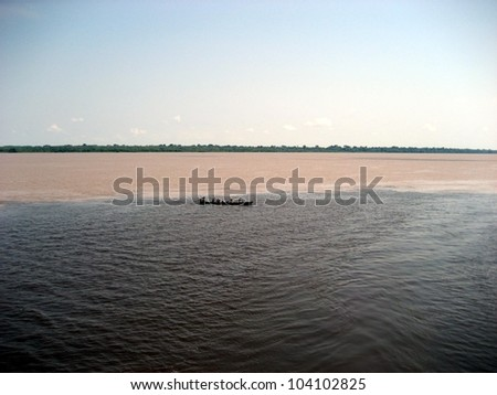 Meeting of the Rio Amaturá (black water) and the Rio Solimoes (muddy water) at Amaturá in the Amazon, Brazil