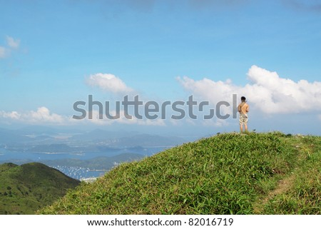 Meeting of the sky. The man on high mountain with the hands lifted above, on a background of blue sky