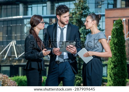 Meeting outside the office. Three successful business people in formal clothes standing on the street to discuss business and keep computers in their hands. Young businessman smiling  - stock photo