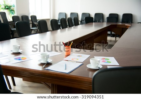 Meeting room with a large table. Paper documents, graphs. Cups for coffee and colored pencils. - stock photo